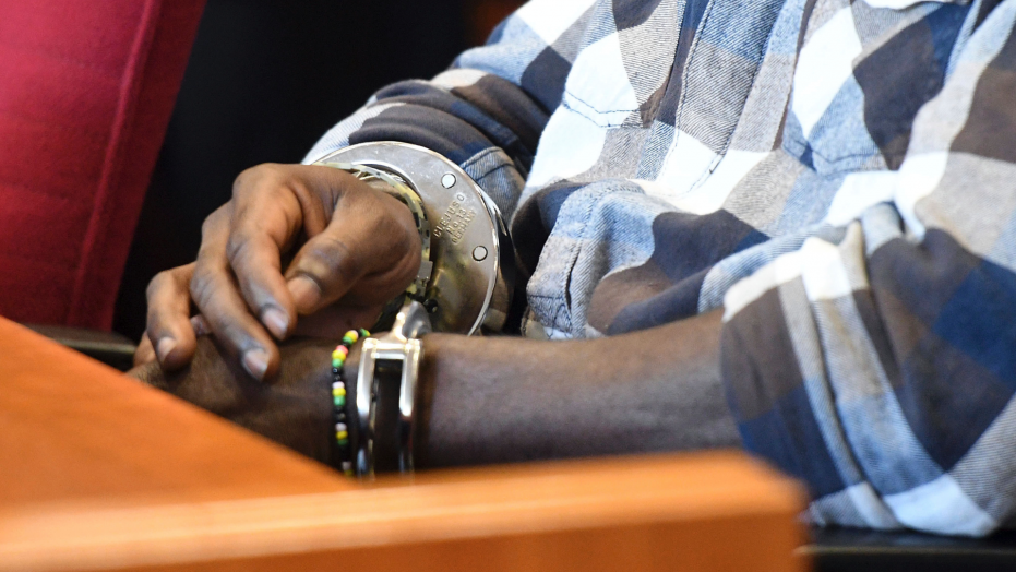 Defendant Eric X. sits in a court room in Bonn, Germany awaiting a verdict in his rape trial.